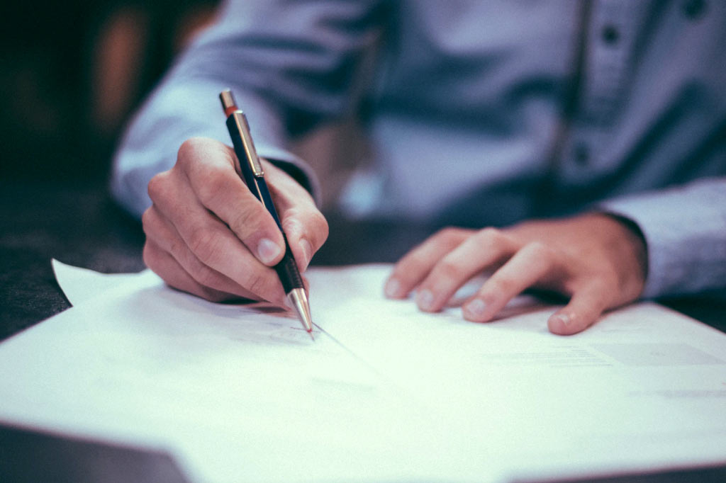 Hands signing a Terms of Service contract